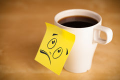 Post-it note with smiley face sticked on cup Royalty Free Stock Photo