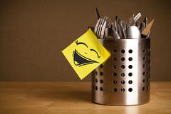 Post-it note with smiley face sticked on cutlery case Stock Images