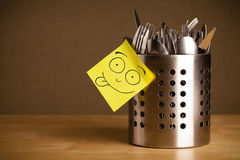 Post-it note with smiley face sticked on a cutlery case Royalty Free Stock Photos