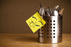 Post-it note with smiley face sticked on cutlery case Royalty Free Stock Images
