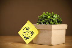 Post-it note with smiley face sticked on flowerpot Stock Image