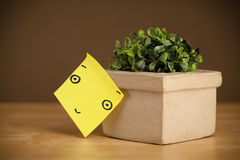 Post-it note with smiley face sticked on flowerpot Stock Photos