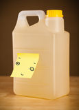 Post-it note with smiley face sticked on a gallon. Drawn smiley face on a post-it note sticked on a gallon Stock Photos