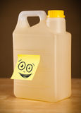 Post-it note with smiley face sticked on gallon. Drawn smiley face on a post-it note sticked on a can Stock Photos