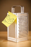 Post-it note with smiley face sticked on a grater Royalty Free Stock Photo