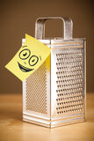 Post-it note with smiley face sticked on grater Royalty Free Stock Photography
