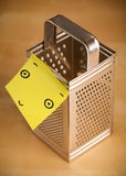 Post-it note with smiley face sticked on a grater Stock Photos
