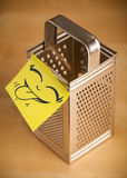 Post-it note with smiley face sticked on a grater Stock Photo
