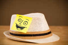Post-it note with smiley face sticked on a hat Stock Photo