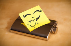 Post-it note with smiley face sticked on hip flask Stock Photos
