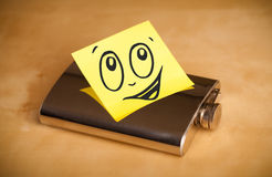 Post-it note with smiley face sticked on hip flask Stock Photo