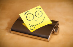 Post-it note with smiley face sticked on a hip flask Royalty Free Stock Photo