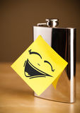 Post-it note with smiley face sticked on hip flask Stock Images