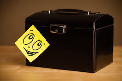 Post-it note with smiley face sticked on jewelry box Royalty Free Stock Photography