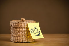 Post-it note with smiley face sticked on jewelry box Stock Photo
