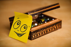 Post-it note with smiley face sticked on jewelry box Stock Photography