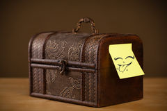 Post-it note with smiley face sticked on jewelry box Royalty Free Stock Images