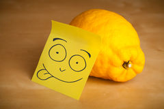 Post-it note with smiley face sticked on a lemon Stock Image