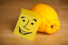 Post-it note with smiley face sticked on a lemon Stock Photos