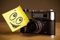 Post-it note with smiley face sticked on photo camera Royalty Free Stock Photo