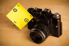 Post-it note with smiley face sticked on a photo camera Royalty Free Stock Image