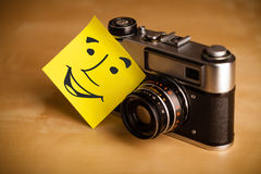 Post-it note with smiley face sticked on a photo camera Stock Image