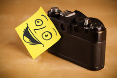 Post-it note with smiley face sticked on photo camera Stock Photo