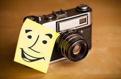 Post-it note with smiley face sticked on a photo camera Royalty Free Stock Photography