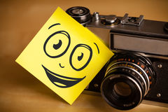 Post-it note with smiley face sticked on photo camera Royalty Free Stock Photography