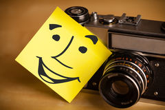 Post-it note with smiley face sticked on a photo camera Stock Photos