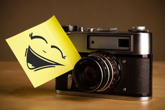 Post-it note with smiley face sticked on photo camera Royalty Free Stock Image