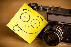 Post-it note with smiley face sticked on a photo camera Royalty Free Stock Photos
