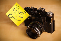 Post-it note with smiley face sticked on a photo camera Royalty Free Stock Images