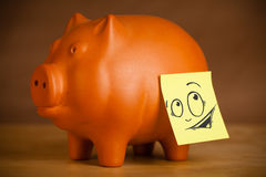 Post-it note with smiley face sticked on a piggy bank Stock Image