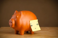 Post-it note with smiley face sticked on piggy bank Royalty Free Stock Images