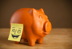 Post-it note with smiley face sticked on a piggy Royalty Free Stock Image