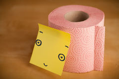 Post-it note with smiley face sticked on a toilet paper. Drawn smiley face on a post-it note sticked on a toilet paper roll Royalty Free Stock Photo
