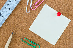 Post-it note and stationary on cork board. Post-it note on cork board with red pin and colorful paper clips Royalty Free Stock Photo