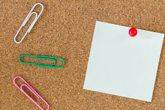 Post-it note and stationary on cork board. Post-it note on cork board with red pin and colorful paper clips Royalty Free Stock Image