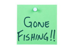 Post it note on wood. In green with gone fishing Stock Images