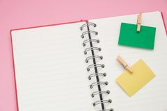 Post it note with wooden clip stick isolated blank notebook. hav. Two post it note with wooden clip stick isolated blank notebook. have pink on background. image Royalty Free Stock Photo