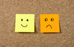 Post it notes on corkboard with smiley and sad cartoon face expression in happiness versus depression concept. Two post it notes stuck on corkboard or message Stock Image
