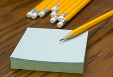 Post-it notes with pencil. Block of post-it notes with yellow pencil on a wooden table Royalty Free Stock Photos