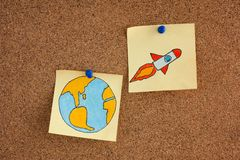 Post it Notes with planet Earth and Space Rocket on bulletin boa royalty free stock photo