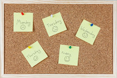 Post-it notes with weekdays and smileys sticked on corkboard Royalty Free Stock Photography