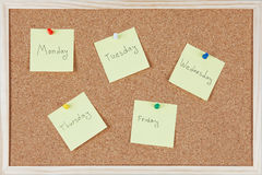 Post-it notes with weekdays sticked on corkboard Stock Photos