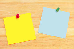Post-It Notes on Wood Desk. Clean post-it notes on a wood background with push pins Stock Images