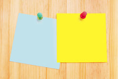 Post-It Notes on Wood Desk. Pair of clean post-it notes on a wood background with push pins Stock Image