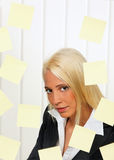Post-it notes and worker. Portrait of blond young businesswoman surrounded by blank post-it notes Stock Photography