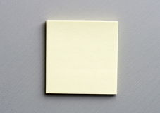 Post-it om grey. Yellow post-it block on grey wooden surface Royalty Free Stock Image